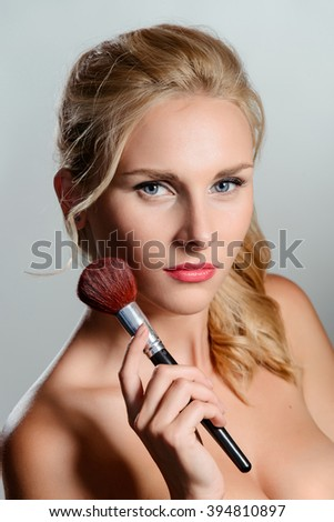 Charming blondie portrait with a brush. Gentle bare shoulders. Delicate long fingers. Ideal retouching. Beautiful eyebrows, lashes and lips. - stock photo