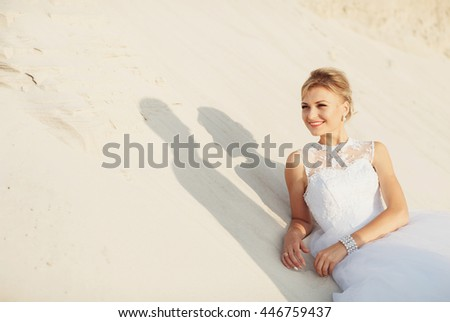 Charming bride is lying on the white sand - stock photo