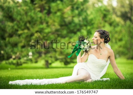 Charming bride sit on grass in the park. - stock photo