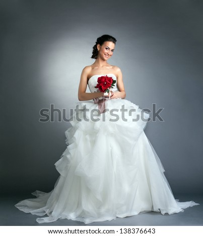 Charming bride with bouquet posing in studio - stock photo