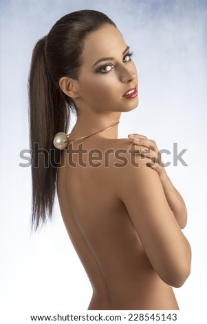 charming brunette girl with stylish make-up and golden necklace showing her sexy nude back and looking in camera  - stock photo