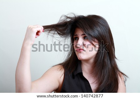 Charming brunette is not happy with fragile hair - stock photo
