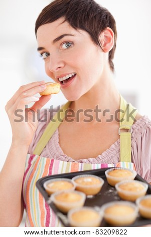 Charming brunette woman showing muffins while eating one in a kitchen - stock photo