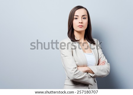 Charming businesswoman. Confident young businesswoman keeping arms crossed and looking at camera while standing against grey background - stock photo