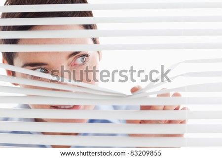 Charming businesswoman peeking through a venetian blind in an office - stock photo