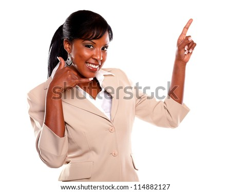 Charming businesswoman pointing up and looking at you while saying call me against white background - stock photo