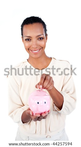 Charming businesswoman saving money in a piggybank against a white background - stock photo