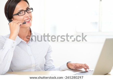 Charming callcenter employee with glasses working on the desk while smiling and looking at you - stock photo