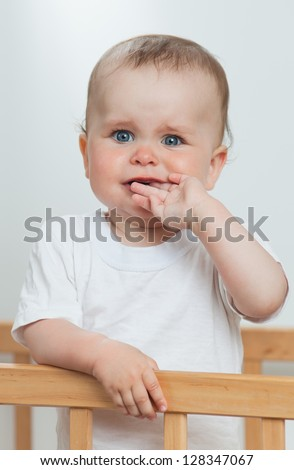 Charming child in the crib. Charming baby is crying looking at camera - stock photo