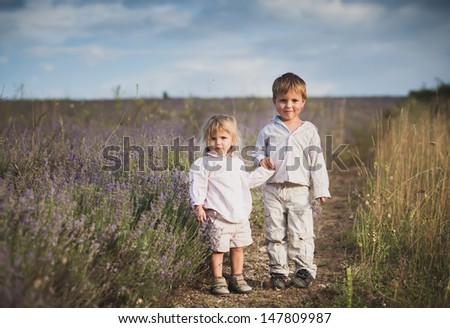 Charming children on lavender field at sunset - stock photo