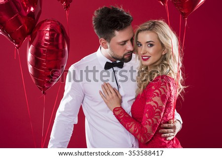 Charming couple holding two bunches of red shiny balloons - stock photo