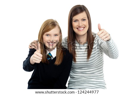 Charming daughter with her mother showing thumbs up sign to the camera. - stock photo