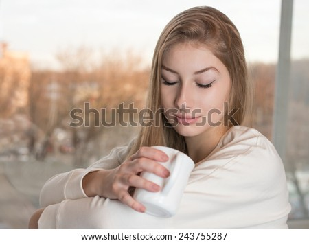 Charming dreamy girl is sitting indoor near the window and enjoying the aroma from a white mug - stock photo