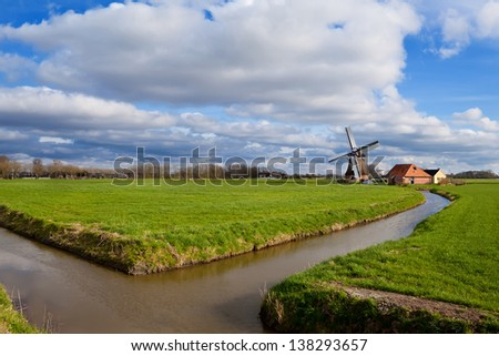 charming Dutch windmill by canal on green grassland, Holland - stock photo