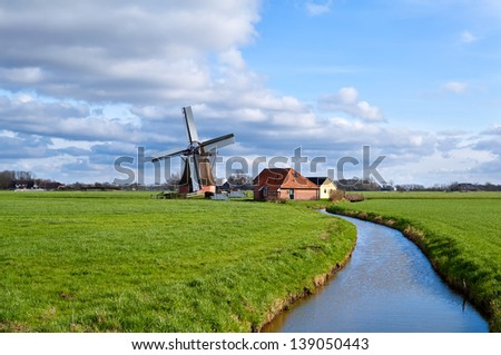 charming dutch windmill on green grasslands by river, Groningen - stock photo