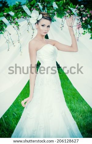 Charming elegant bride under the wedding arch. Wedding dress and accessories. Wedding decoration.  - stock photo