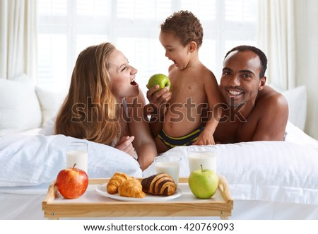 Charming family having breakfast in parents bed at home. Breakfast in bed - stock photo