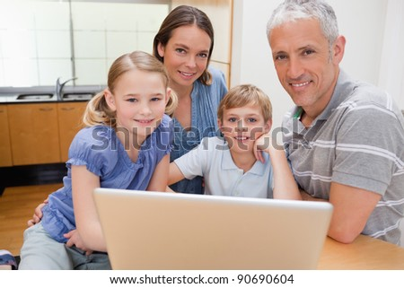 Charming family using a laptop in their kitchen - stock photo