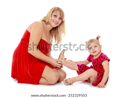 Charming fashionable mom puts on her little shoes adorable daughter.Isolated on white background, Lotus Children's Center. - stock photo