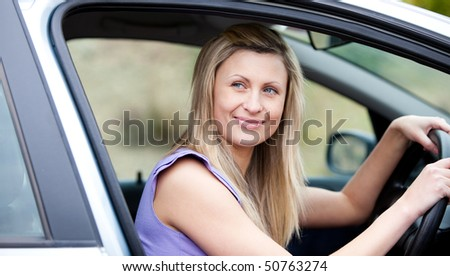 Charming female driver at the wheel in her new car - stock photo