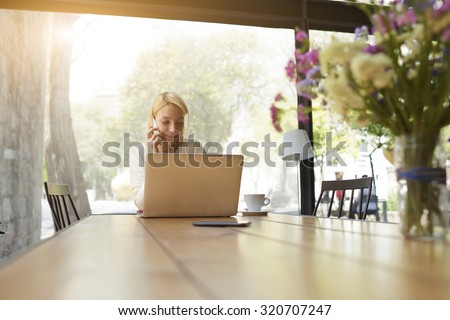 Charming female speaking on her cell telephone with lovely smile while sitting at wooden table with open laptop computer, women having smart phone conversation looking happy and pleased with call - stock photo