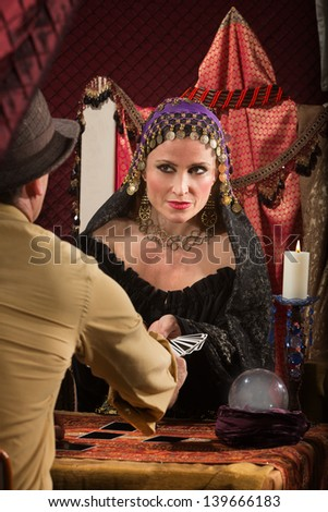 Charming fortune teller giving man a tarot card - stock photo