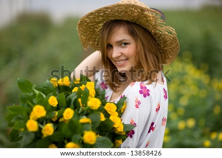 Charming gardener - young girl in flower bed with bouguet of yellow roses - stock photo
