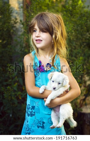 Charming girl holding a puppy - stock photo