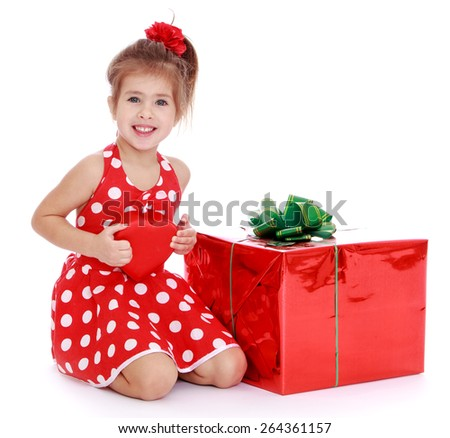 Charming girl in a red dress with white polka dots is holding a red heart, isolated on white background sitting next to a big box - stock photo