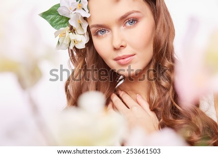 Charming girl looking at camera out of spring blossom - stock photo