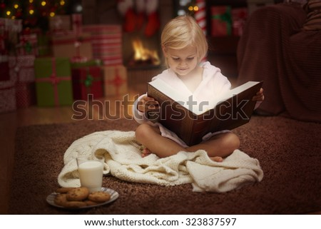 Charming girl reading some Christmas tales   - stock photo