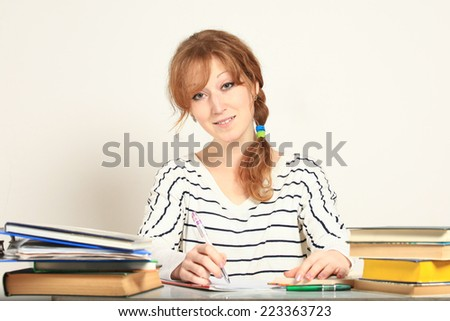 Charming  girl sitting at table with books studying writing in notebook - stock photo