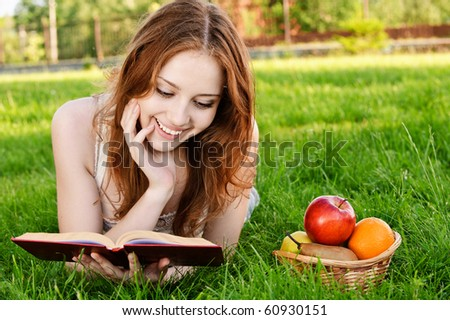 Charming girl with apples lies on green grass and reads book. - stock photo