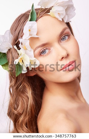 Charming girl with white flowers in her long curly hair looking at camera - stock photo