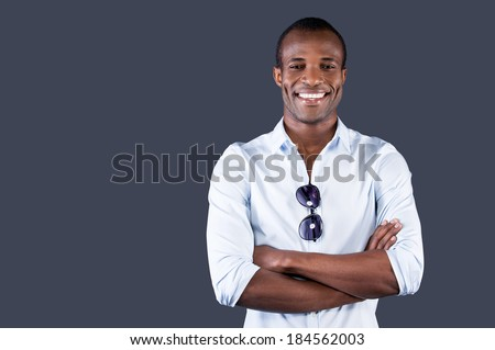 Charming handsome. Handsome young black man in blue shirt keeping arms crossed and smiling at camera while standing against grey background - stock photo