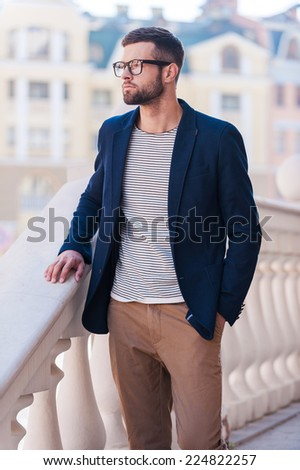 Charming handsome. Handsome young man in eyeglasses and smart casual wear looking away while standing outdoors - stock photo