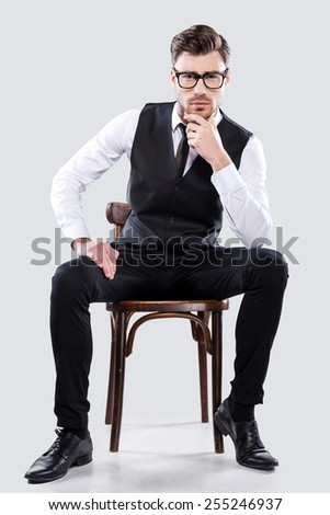 Charming handsome. Handsome young man in formalwear holding hands in pockets and looking at camera while standing against grey background - stock photo
