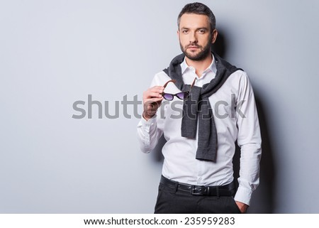 Charming handsome. Handsome young man in in smart casual wear holding sunglasses and looking at camera while standing against grey background - stock photo