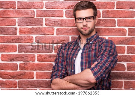 Charming handsome. Handsome young man keeping arms crossed and looking at camera while standing against brick wall - stock photo