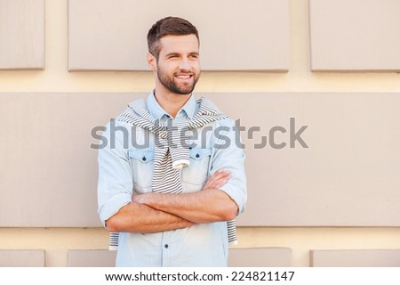 Charming handsome. Handsome young man keeping arms crossed and smiling while standing in front of the textured wall outdoors - stock photo