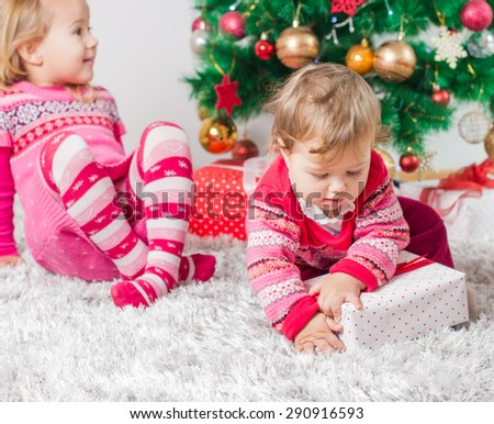 Charming happy children open Christmas presents on the floor and tree with New Year decoration at home. - stock photo