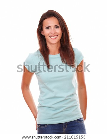 Charming hispanic woman on blue t-shirt smiling at you while standing on isolated studio - stock photo