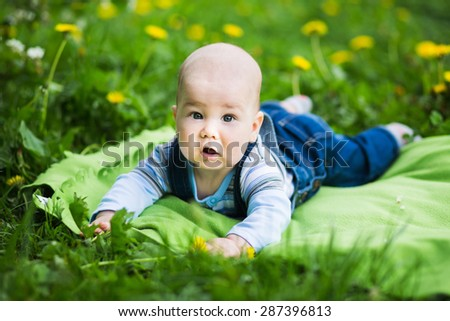Charming infant in jeans coveralls lying on the lawn in the summer park - stock photo