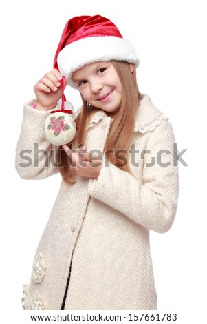 charming joyful little girl with long blond hair in Santa hat holding christmas ball isolated on white - stock photo