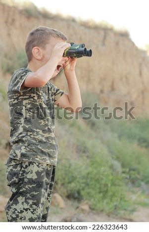 Charming little boy in a camouflage play war binokol looking into outdoor - stock photo