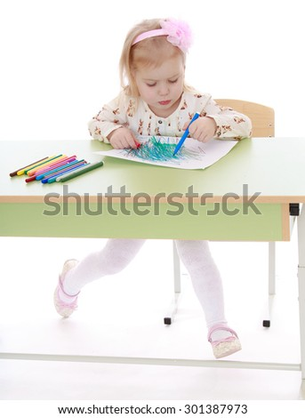 Charming little Caucasian girl with blond hair on his head that adheres to the rim in the form of roses sitting at the table and draws a felt-tip pen. The girl is engaged in drawing goes to art school - stock photo
