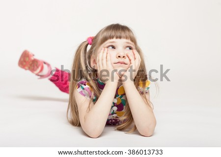 Charming little girl dreaming and lying on the floor, white background - stock photo