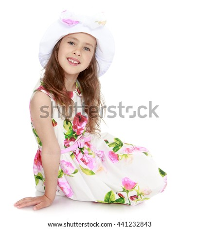Charming little girl in a smart white dress with roses and a white cap , sitting on the floor - Isolated on white background - stock photo