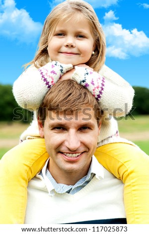 Charming little girl posing with her father against beautiful nature background - stock photo