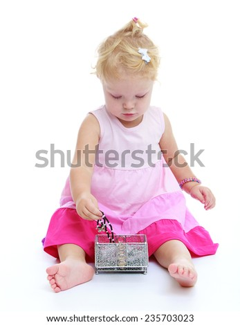 charming little girl with bare feet sitting on the floor and pulls out of the box my mother's beautiful decorationsWhite background, isolated photo. - stock photo